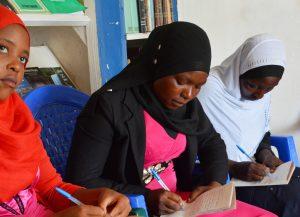 Three Muslim girls writing