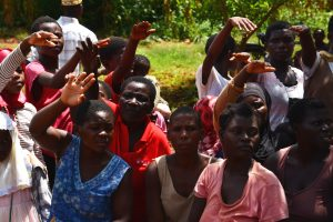 A group of Malawians, mainly womne, raising their hands