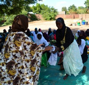 Woman being given a prize as part of a HIV quiz, Nchalo, Malawi